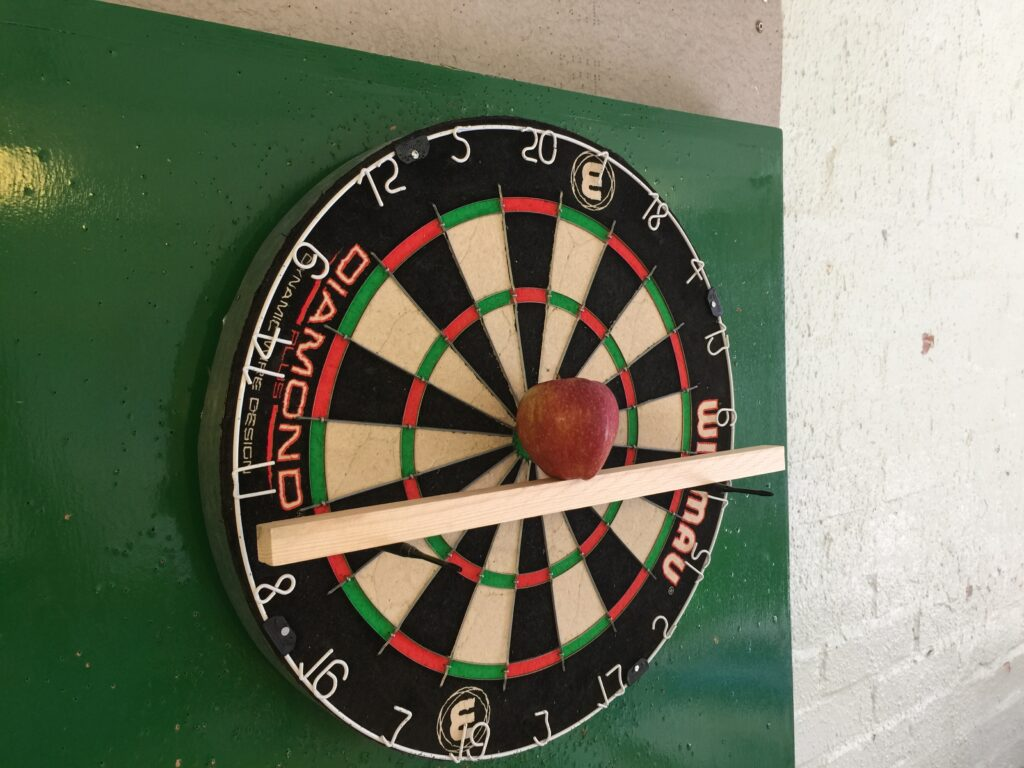 Apple in front of the dartboard
